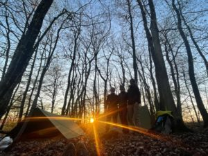 3 Wanderinnen stehen vor ihrenTarpzelten mit Sonnenuntergang im Hintergrund